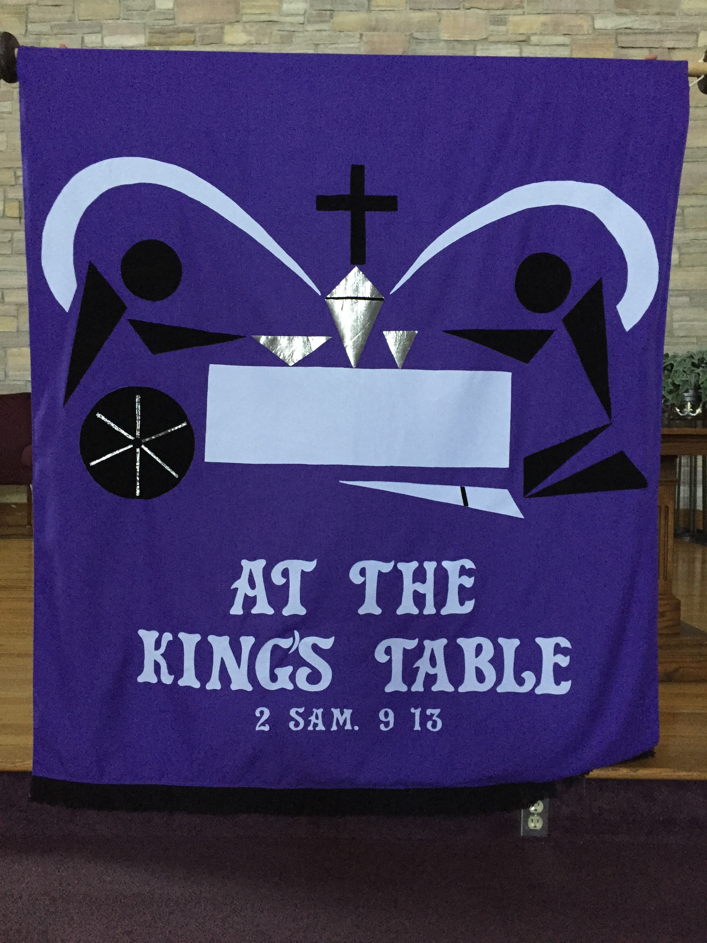 Picture of people gathered at a communion table, one in a wheelchair