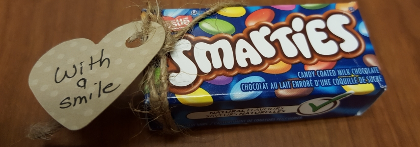 """Box of Smarties candy, with handmade label attached that says, """"With a Smile."""""""