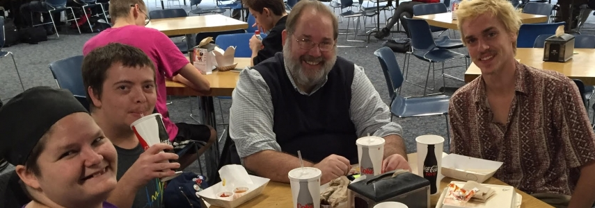 Peter Gordon sits with Grand Rapids Community College Students in the GRCC cafe.