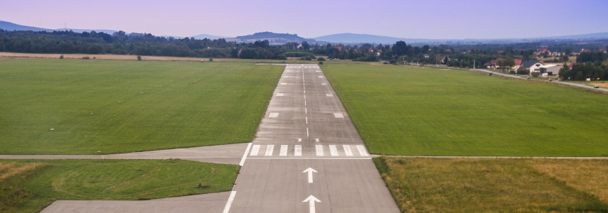 an airport runway on a sunny day with some hills in the distance