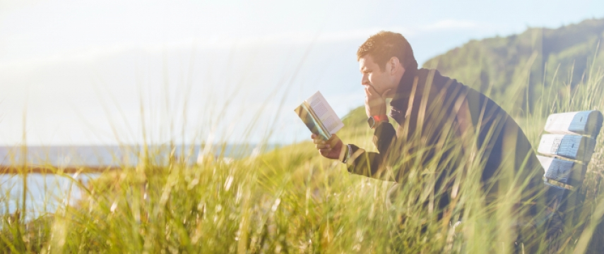 man reading book on a bench outside