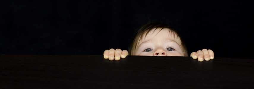 a baby peeks over the edge of a dark surface
