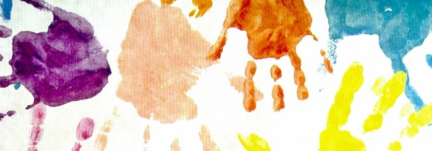 On a white background, there are many handprints in many different paint colors.