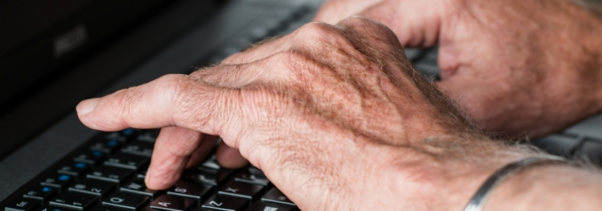wrinkled hands type on a laptop keyboard