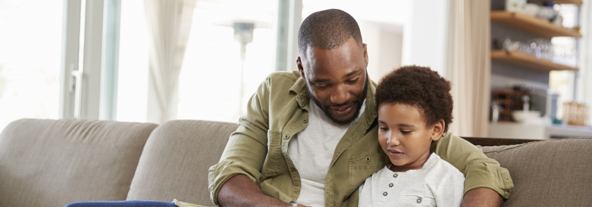 a father and son read a book together on a couch