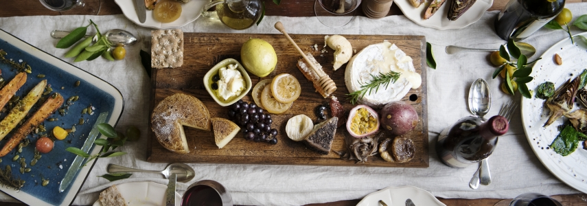 On a wood table, plates with half-eaten food surrounds a centerpiece with various cheeses, grapes, and other food dishes.