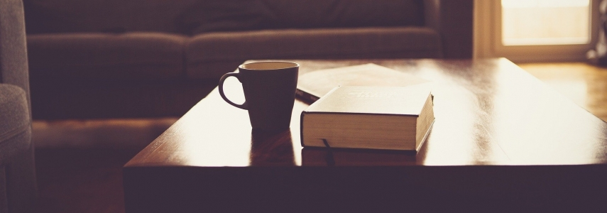 A mug and large book sit on a coffee table in a living room