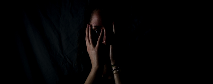a silhouette of a woman in the dark, covering her face with her hands