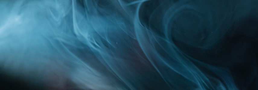 a cloud of blue smoke billows in front of a black background