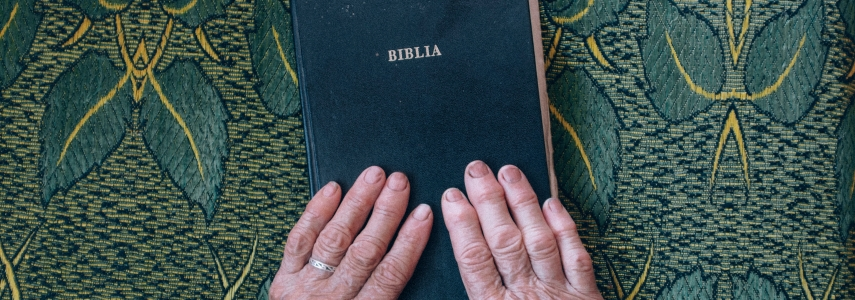 "On a table cloth, old hands rest on a black book with the word ""Biblia"" in gold lettering"