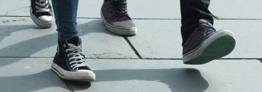 two pairs of feet stroll next to each other on a paved walkway
