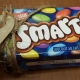 "Box of Smarties candy, with handmade label attached that says, ""With a Smile."""