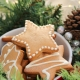 a bowl of star-shaped Christmas cookies sits in an evergreen garland with pinecones