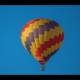 a red, yellow, and blue checkered hot air balloon lifts off into the blue sky