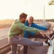 In the pedestrian lane of a bridge, an elderly man and a young man, both in athletic gear, stretch their legs