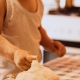 a child touches bread dough on a red and white table cloth