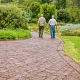 Two old white men walk down a brick path in a garden