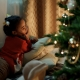 girl in red sweater lies down by Christmas tree