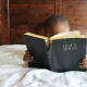 small child reading large Bible in bed